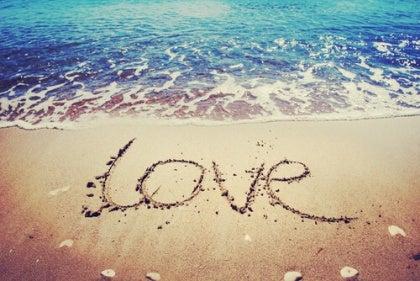 """""""Love"""" skrevet i sandet ved et blåt hav"""