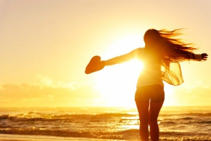Kvinde på strand nyder solnedgang