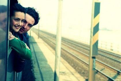 Et par stikker hovederne ud af vinduet på et tog