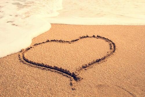 Et hjerte tegnet i sandet ved et hav