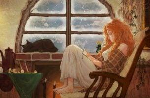 Pige sidder i en lænestol og er ved at læse bog