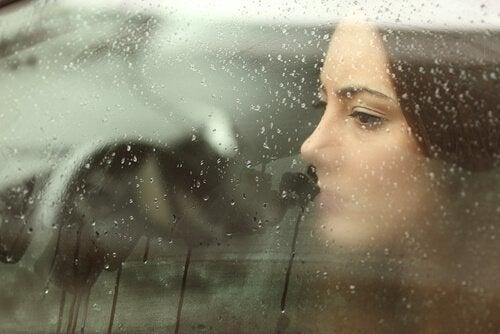 Kvinde kigger ud af vindue og prøver at hele sår