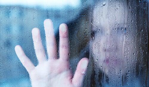 Kvinde sætter hånd mod vådt vindue