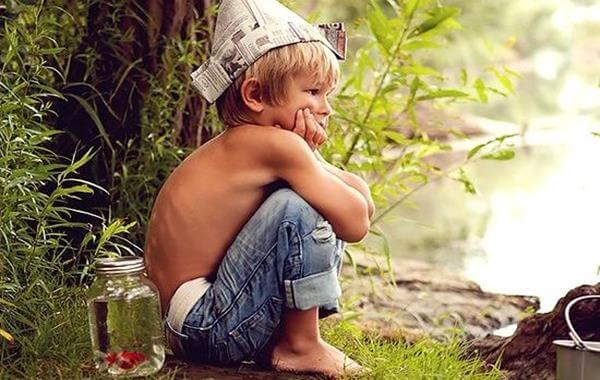 En dreng sidder på hug med avishat på