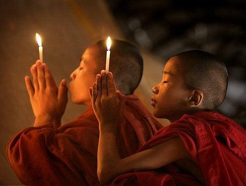 Buddhistiske børn beder med lys