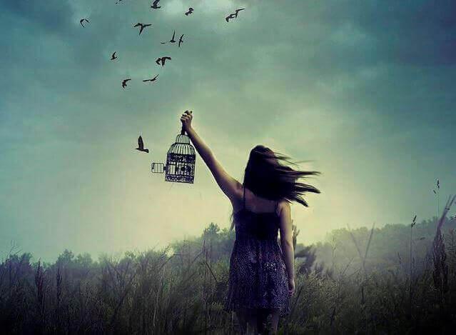 En kvinde holder et fuglebur og slipper fuglene fri