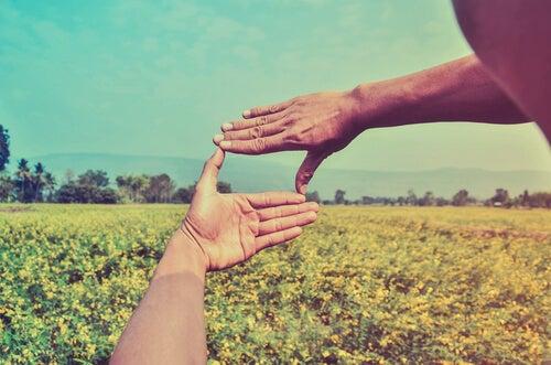 To hænder danner en ramme om et landskab