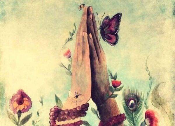 To hænder er samlet med blomster og sommerfugle omkring