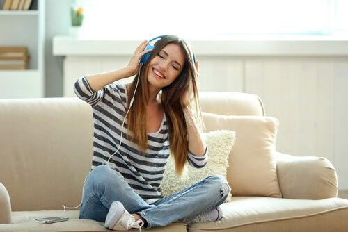 Smilende kvinde lytter til musik