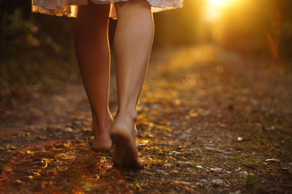Kvinde går barfodet mos solen og væk fra sin sorg