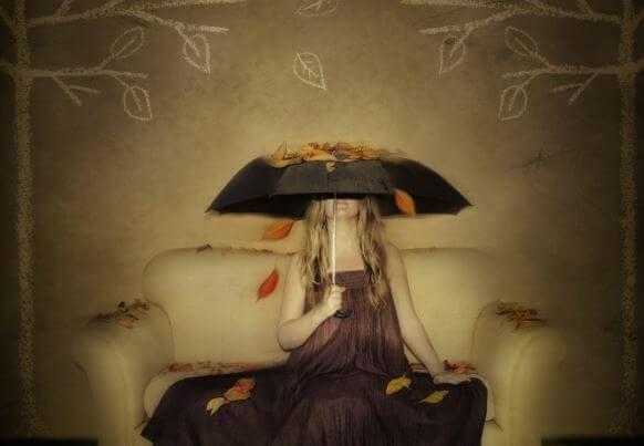 Kvinde sidder i sofa med paraply med blade liggende ovenpå