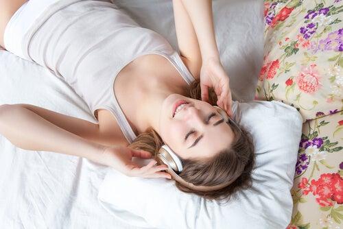 Kvinde ligger på seng og lytter til musik
