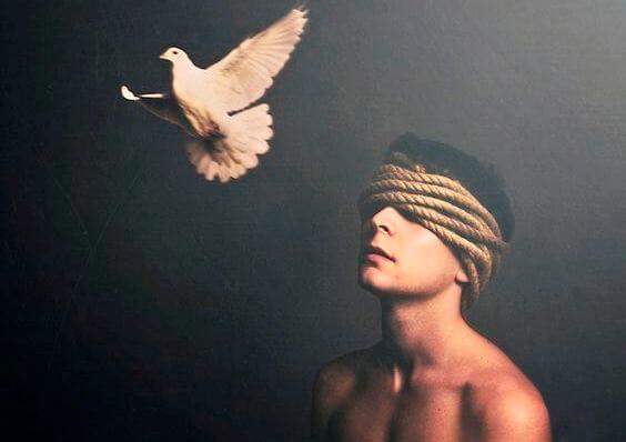 En mand med bind for øjnene og en flyvende, hvid due