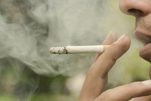 Fingre holder en cigaret med røg omkring