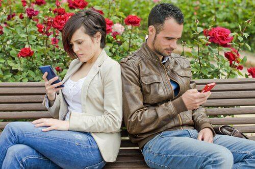 Et par sidder med ryggen mod hinanden og kigger på hver deres telefoner, som er en af nutidens forholds forhindringer