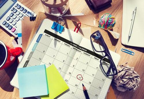 Et skrivebord med en kalender, briller og notesblok