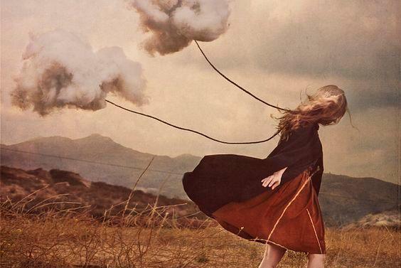Trist pige går med skyer bundet fast i en snor