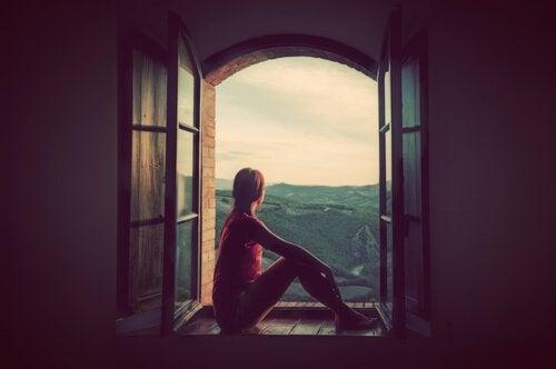 En kvinde sidder i et vindue og kigger ud på landskabet