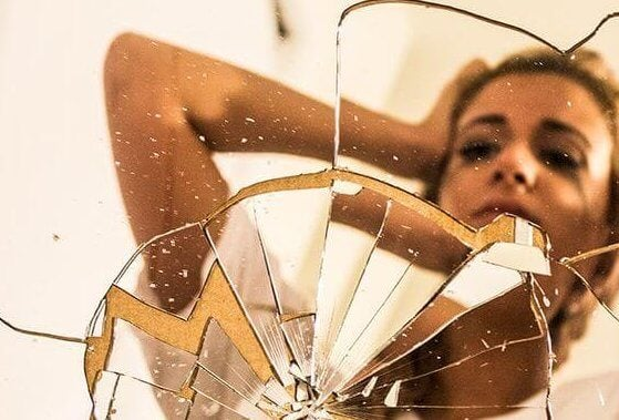 Kvinde foran ødelagt spejl, som hun har smadret på grund af et panikanfald