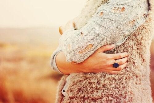 Kvinde krammer sig selv, da det er vigtigt at pleje dig selv