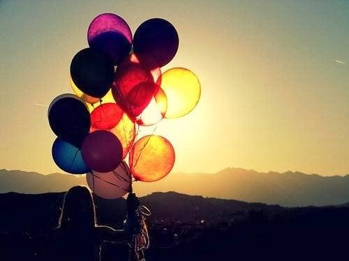 Kvinde med balloner mod solen