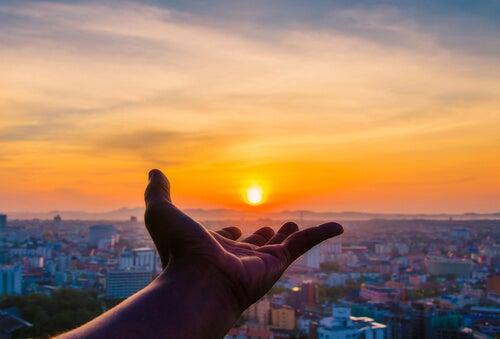 En hånd rækker ud mod en solnedgang som symbil på, at man skal værdsætte det, man har