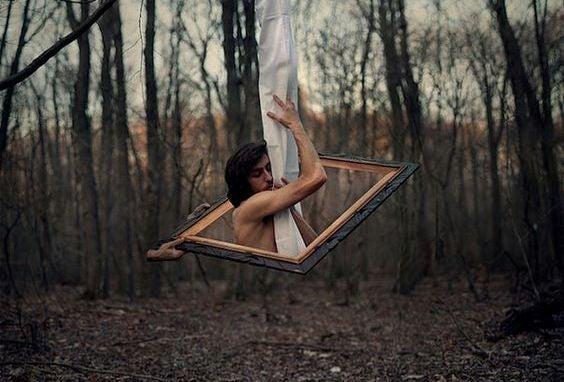 Mand i en ramme i en skov klynger sig til et stykke stof og prøver at værdsætte det, han har