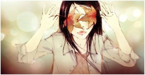 Kvinde gemmer sine øjne bag blade