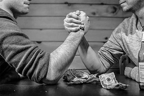 To mænd lægger arm for penge