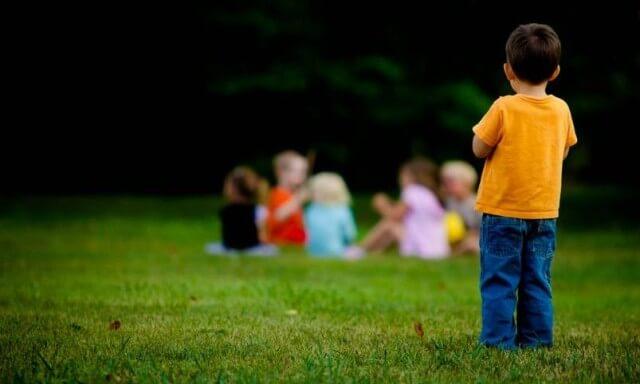 Børn leger, dreng står udenfor vennekredsen