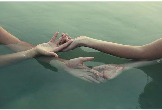 Hænder rører ved hinanden i vand