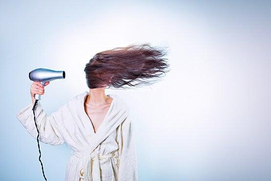 Kvinder blæser sit hår med en hårtørrer