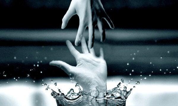 Hånd rækker ud efter anden hånd, der er ved at drukne