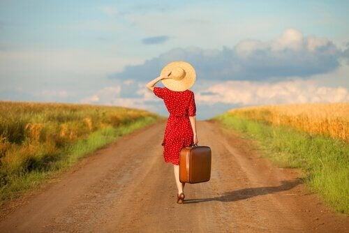 Kvinde med hat og kuffert går på vej for at glemme sin fortid