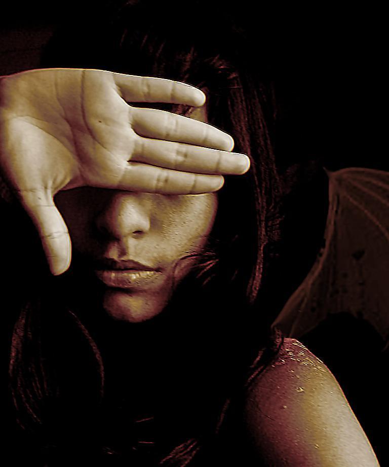 Kvinde dækker øjne med hånden