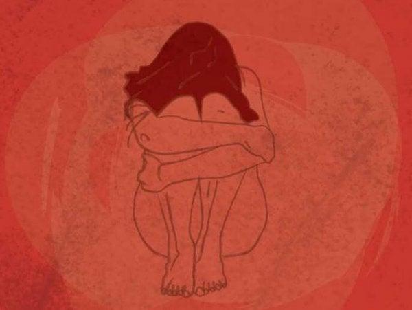 Kvinde i smerter omfavner sig selv