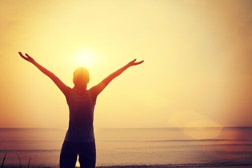 Person har hænderne oppe i luften foran sol