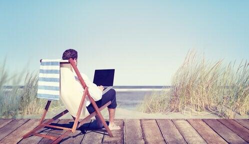 Mand med computer på strand arbejder ifølge Pareto-princippet