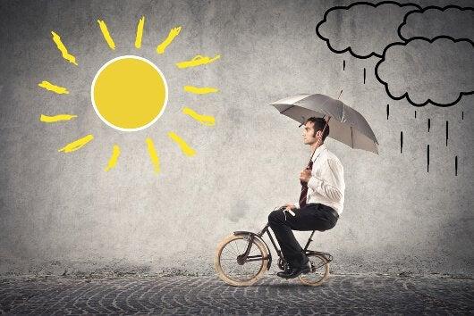 Mand på cykel følger positiv psykologi og kører fra regn til solskin