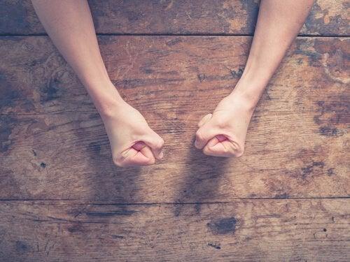 Knyttede næver på bord viser en person, der er opslugt af vrede