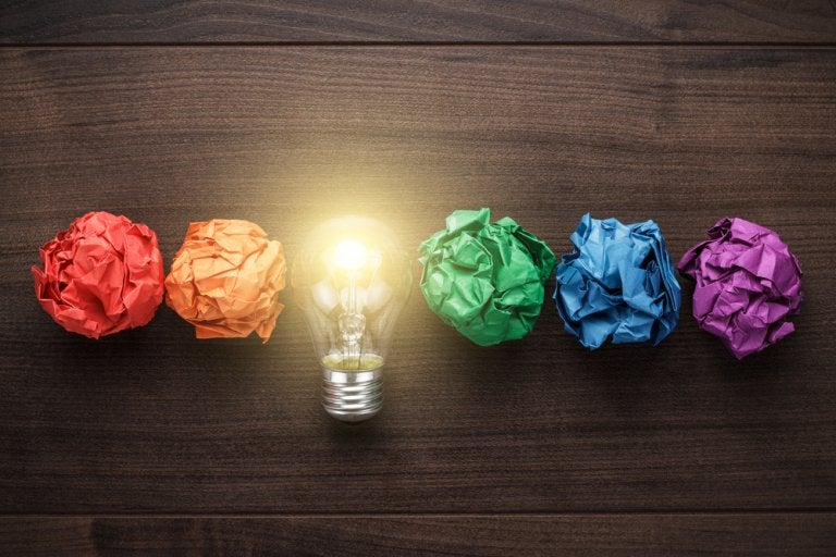 Lysende pære mellem farvede papirskugler viser kreativitet