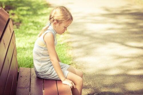 En trist pige alene på en bænk