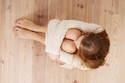 Kvinde på gulv krammer sig selv