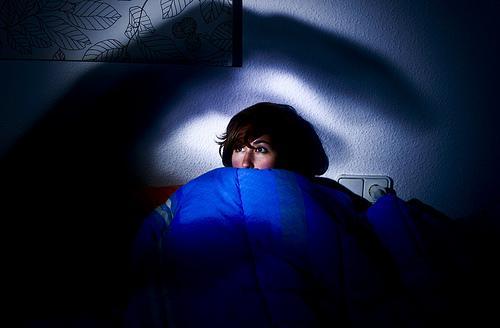 Skræmt kvinde i en seng symboliserer søvnlammelse