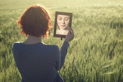 En kvinde holder et spejl på en mark