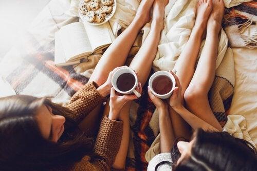 To piger drikker te i seng for at give hinanden social støtte