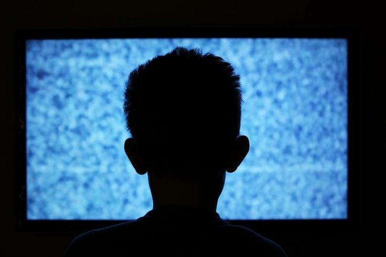 Mand ser tv i mørke