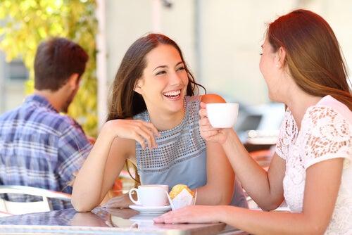 To veninder drikker kaffe sammen, griner og drager nytte af sociale evner