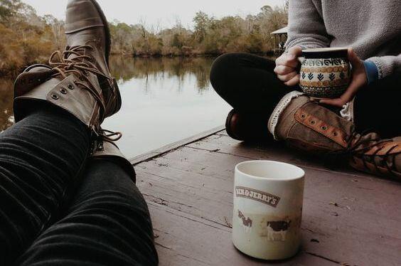 To venner drikker kaffe sammen på en bro