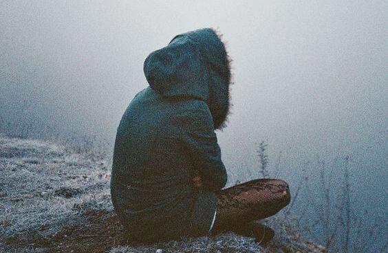 Ensom person sidder i kulde og sørger over, hvordan venner skuffer